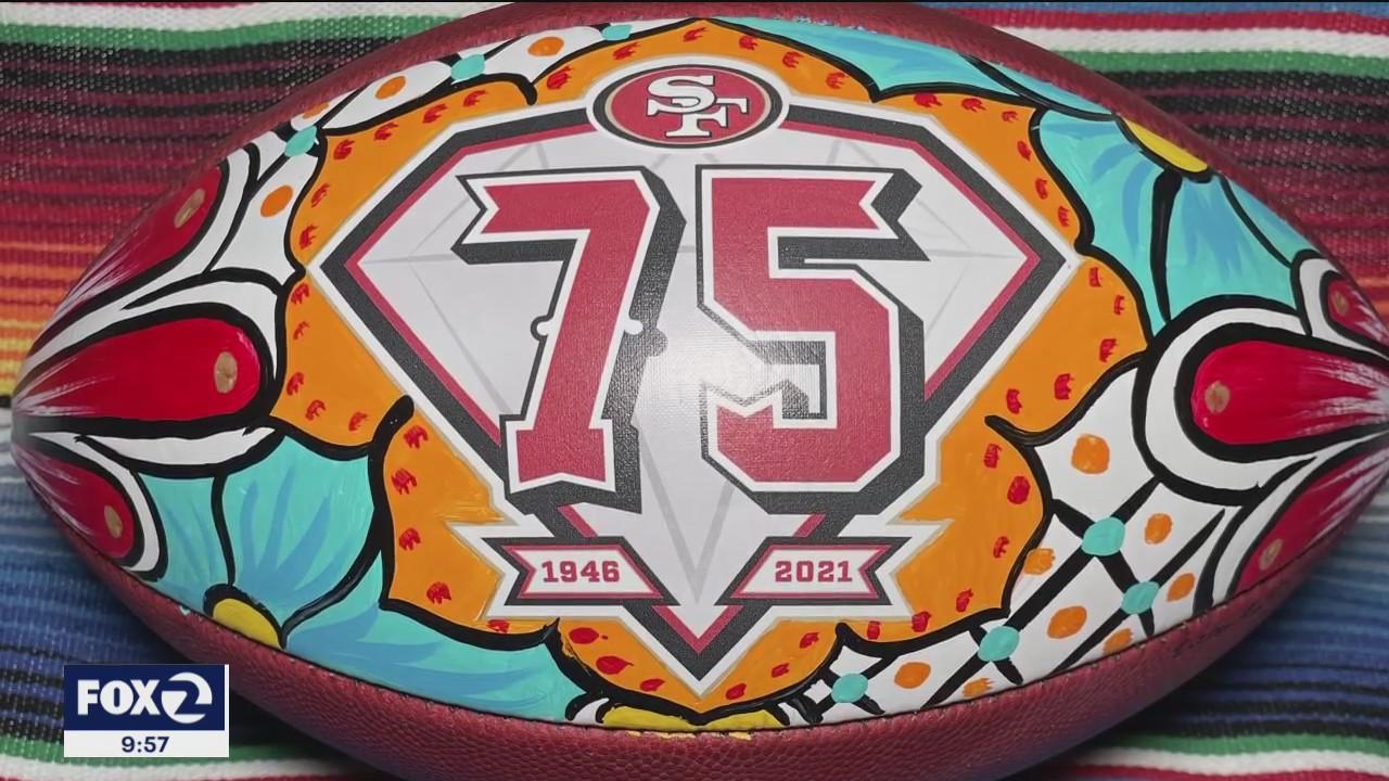 Latinx artist hand-painting footballs